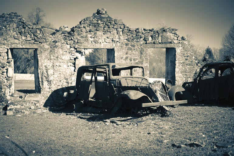 Oradour-sur-Glane- sepia photo of tumbling down ruin sof walls and rusting car in front
