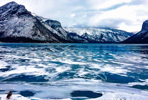 Lake-Minnewanka-banff-National-Park - blue water with ice on top and mountains in the background