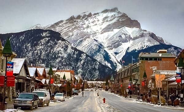 banff-Town-at-Christmas - main street with shops and houses either side and a huge mountain in the background