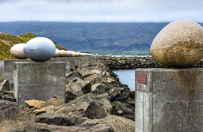many granite eggs on small pedestals lining the harbour front, iceland