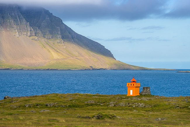 orange lighthouse overlloking a bay with a huge mountain as backdrop, iceland