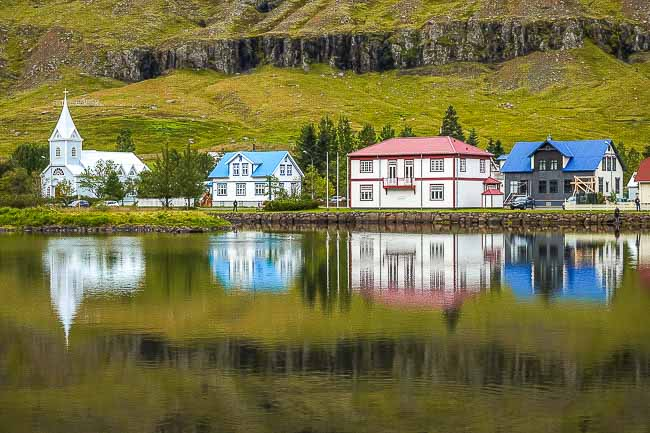 coloured buildings with reflections on a fjord, iCeland