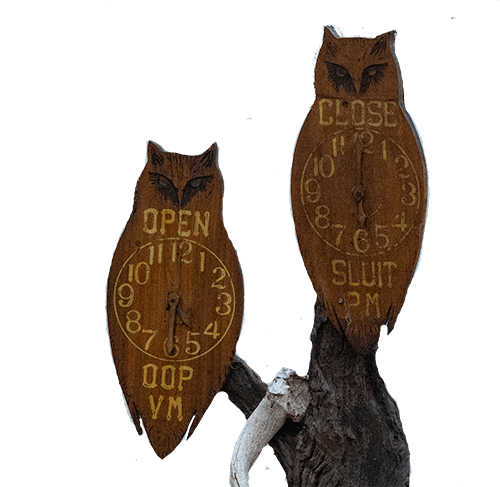 two wooden owls with clock hands showing Kruger rest camp open and closed times