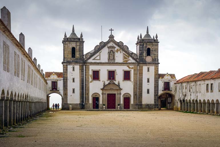 Nossa-Senhorado-Cabo-Church - a white church with red rimmed windows and doors and two long buildings attached