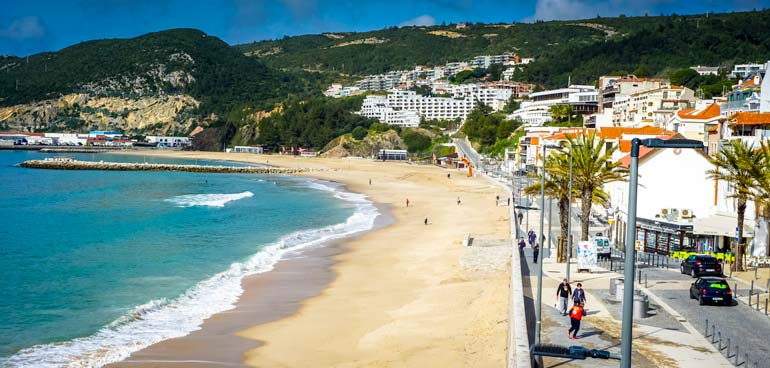 Sesimbra-beach-portugal - long stretch of beach with trees and houses in the background