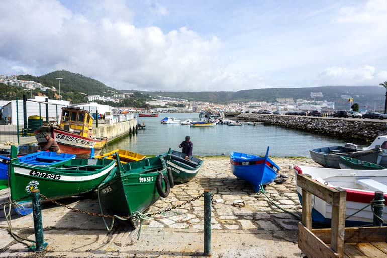 Sesimbra. jetty with colourful boats and view of the green hils behind sesimbra bay