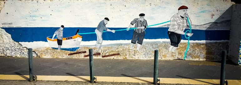 Sesimbra street art with fisherman pulling a boat out of the water