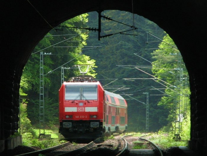 red train about to go through a tunnel
